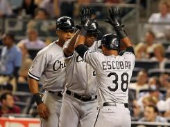 White Sox right fielder Alex Rios, left, and shortstop Eduardo Escobar (38) celebrate scoring after Dayan Viciedo hit a three-run home run in the ninth inning against the New York Yankees.