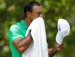 Tiger Woods wipes sweat from his face before he tees off the first hole during the third round of the AT&amp;T National at Congressional Country Club.