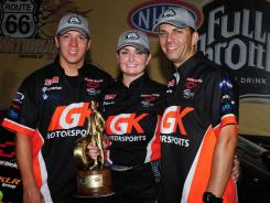Erica Enders, center, holds a victory trophy for the first time in the Pro Stock series. Joining her Sunday in Joliet, Ill., are crew chief Dave Connolly, left, and boyfriend (now fiance) Richie Stevens.