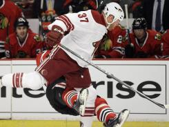 Phoenix's Raffi Torres delivers a late hit against Chicago's Marian Hossa during an April 17 games.