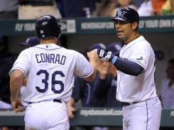Tampa Bay's Brooks Conrad celebrates with teammate Carlos Pena after scoring the go-ahead run on Mark Teixeira's error in the seventh inning.