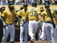 Oakland's Brandon Moss is congratulated by teammates after hitting a home run off Boston Red Sox's Aaron Cook in the second inning.