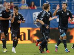 Graham Zusi of the Sporting Kansas City celebrates his second half penalty kick goal with teammates during their match against the Montreal Impact at Saputo Stadium.
