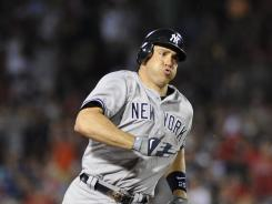 New York Yankees first baseman Mark Teixeira runs to third base after hitting a triple during the seventh inning against the Boston Red Sox at Fenway Park.