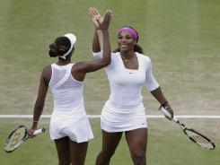A high-five for Serena Williams, right and Venus Williams, who move Friday into the women's doubles final after defeating Liezel Huber and Lisa Raymond.