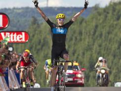 Britain's Christopher Froome celebrates as he crosses the finish line ahead of Australia's Cadel Evans, left, to win the seventh stage of the Tour de France on Saturday.