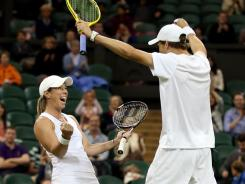 Lisa Raymond and Mike Bryan celebrate after winning their defeating Elena Vesnina of Russia and Leander Paes of India in mixed doubles.