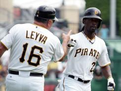 Pirates coach Nick Leyva greets Andrew McCutchen after the first of his two home runs.