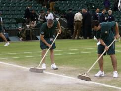 The crew starts the process of cleaning up the grounds after Wimbledon. The beaten-down, brown grass is expected to be green again in time for the start of tennis at the Olympics in 20 days.