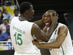 Olumide Oyedeji, left, celebrates with teammate Derrick Obasohan after the team defeated the Dominican Republic to secure a berth in the London Olympics.