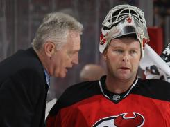 Larry Robinson confers with New Jersey Devils goalie Martin Brodeur during the playoffs.
