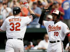Catcher Matt Wieters and center fielder Adam Jones, high-fiving during a June game, are two of the young, budding stars on which the Orioles have pinned their hopes.
