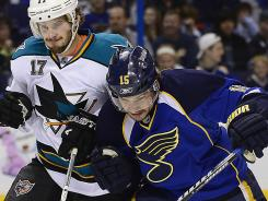 Jamie Langenbrunner, right, battling San Jose's Torrey Mitchell for the puck, is returning for a second season in St. Louis.