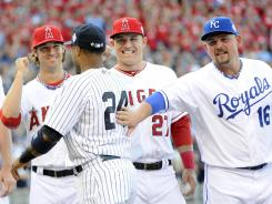 The Yankees' Robinson Cano, center, gets a pat on the back from the Royals' Billy Butler, right, as Cano is introduced to a chorus of boos before Tuesday's All-Star Game.