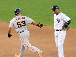 Hand out: Melky Cabrera tries to high five American League infielder Robinson Cano while rounding the bases after a home run Tuesday night. Cabrera and teammate Pablo Sandoval combined for five RBI.
