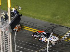 Tony Stewart crosses the finish line first at the Coke Zero 400.
