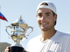 John Isner is the defending champion at Newport, shown here holding the trophy. He won Tuesday in his opening match.