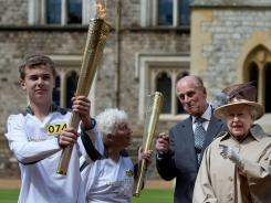 Britain's Queen Elizabeth II, right, her husband Prince Philip, second right watch as torch bearer Phil Wells, left, leaves carrying the Olympic flame at Windsor Castle, England.