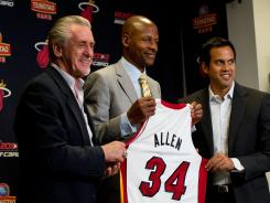 Ray Allen, center, holds up his jersey next to Heat President Pat Riley, left, and head coach Erik Spoelstra, right, during a press conference Wednesday in Miami.