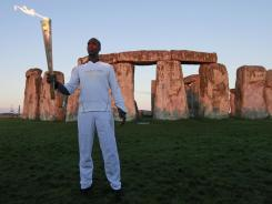 U.S. Olympian sprinter Michael Johnson, who won four Olympic gold medals and eight world championship gold medals, holding the Olympic Flame at Stonehenge, England.