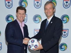 New York Cosmos Chairman Seamus O'Brien, left, and NASL Commissioner David Downs commemorate the franchise's return to the NASL.