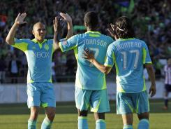 Seattle Sounders' Eddie Johnson, center, is congratulated by teammates after scoring the opening goal in a 4-1 win over Chivas USA. Seattle advanced to its fourth consecutive U.S. Open Cup final with the win.