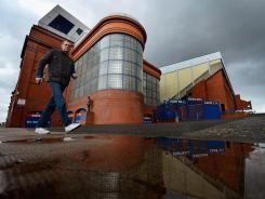 A man walks past Ibrox Stadium, home of Glasgow Rangers. Scottish clubs voted for the 54-time SPL champions to be dropped to the country's fourth tier of professional soccer.