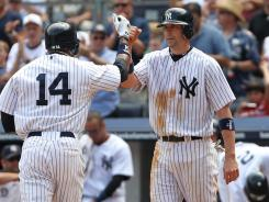 New York Yankees catcher Chris Stewart (19) high fives center fielder Curtis Granderson (14) as they score during the third inning against the Los Angeles Angels at Yankee Stadium.