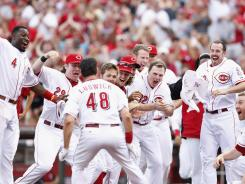 Ryan Ludwick is greeted by his Reds teammates at home plate after hitting a walk-off home run in the 10th inning against the Cardinals.