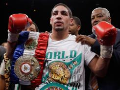 Danny Garcia celebrates his victory over Amir Khan during their WBC/WBA light welterweight title fight Saturday in Las Vegas. Garcia improved to 24-0 with the fourth-round knockout.