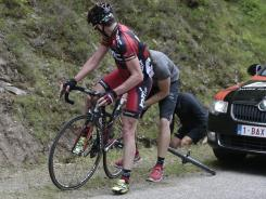 Team mechanics help defending champion Cadel Evans of Australia after he got a flat tire on the Mur de Peguere climb during the 14th stage of the Tour de France.