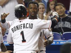 The Marlins' Emilio Bonifacio (1) and Hanley Ramirez (2) hug after Bonifacio put down a sacrifice bunt that scored Justin Ruggiano in the seventh inning.