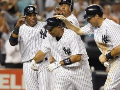 Raul Ibanez, front, is congratulated by Yankees teammates, from left, Robinson Cano, Alex Rodriguez and Mark Teixeira after hitting a grand slam in the eighth inning.