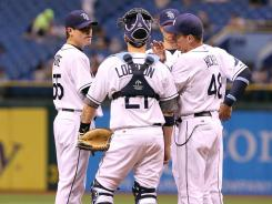 Tampa Bay Rays starting pitcher Matt Moore, left, talks with catcher Jose Lobaton nd teammates on the mound in the fourth inning against the Cleveland Indians.