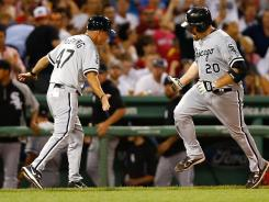Kevin Youkilis of the Chicago White Sox is congratulated by third base coach Joe McEwing after hitting a three run home run in the fourth inning.