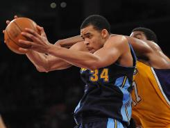 Nuggets center JaVale McGee grabs a rebound in front of Lakers center Andrew Bynum in a May 12 NBA playoff game.
