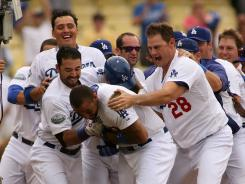 Matt Kemp is mobbed by teammates after his 12th-inning walk-off home run.