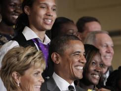 With star center Brittney Griner looming in the background, President Barack Obama poses for photos with the team and coach Kim Mulkey, left.