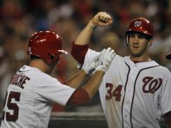 Nationals first baseman Adam LaRoche is congratulated by teammate Bryce Harper after LaRoche's two-run homer in the sixth inning of Washington's 4-3 win.