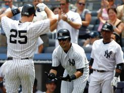 The Yankees' Mark Teixeira is congratulated by teammate Nick Swisher after hitting a two-run homer in the first inning, his 19th home run of the year.