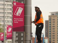 workman erects signage instructing spectators to have their tickets ready at the edge of the Olympic site on July 17 in London.