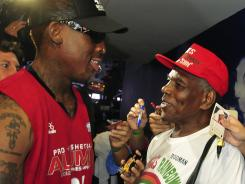 NBA star Dennis Rodman, left, shakes hands with his estranged father Philander Rodman Jr. after an exhibition game in Manila, Philippines. The two finally met after 42 years of separation.