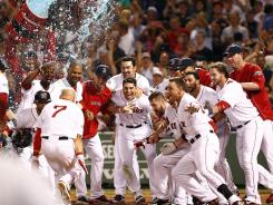 Red Sox players greet Cody Ross at home plate after his three-run walk-off homer in the ninth inning.