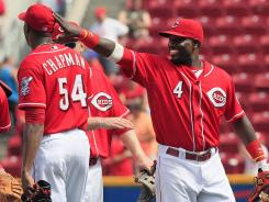 Brandon Phillips pats reliever Aroldis Chapman on the head after the Reds rallied for a 7-6 win over the Diamondbacks