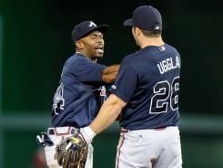 Atlanta's Michael Bourn and Dan Uggla celebrate after coming back from a nine run deficit to beat the Nationals 11-10 in extra innings.