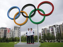 Andy Murray, left, and his brother Jamie pose for photos with the Olympic rings at the Athletes' Village at the Olympic Park.