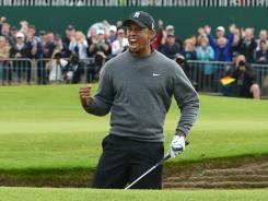 Tiger Woods chips in for birdie out of a greenside bunker on the 18th hole to complete a second-round 67 on Friday at the British Open.