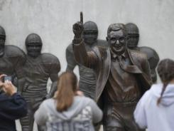Visitors gather around the statue of former Penn State football coach Joe Paterno that stands outside Beaver Stadium on Saturday in State College, Pa.