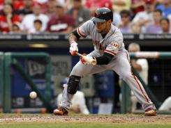 The Giants' Gregor Blanco bunts for an RBI single in the 10th inning against the Phillies, giving San Francisco a 6-5 lead.