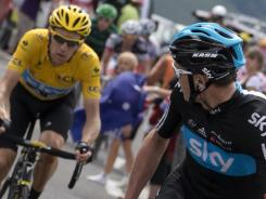 Great Britain's Christopher Froome, right, looks over his shoulder at overall leader Bradley Wiggins as they ride in the 17th stage of the Tour de France.